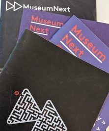 "Four conference brochures laid on top of each other with the word ""MuseumNext"" in the top right hand corner"