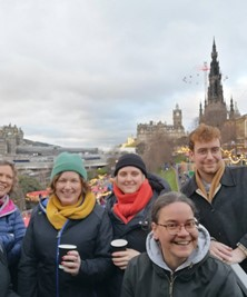 A group of MGS staff outdoors in winter with the Scots Monument and Edinburgh skyline behind them