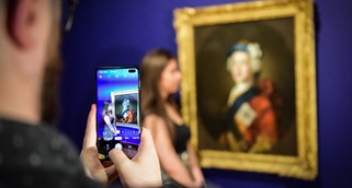 A white man taking a picture with his mobile phone of a young white woman standing next to a painted portrait of Bonnie Prince Charlie at Perth Museum (Katie Adams and David McLeod)