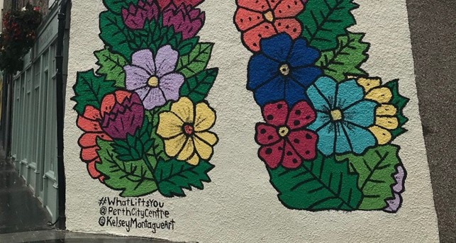 Painted mural on the side of a tall white building of brightly coloured flowers. (#WhatLiftsYouUp Kaley Montague CPK)