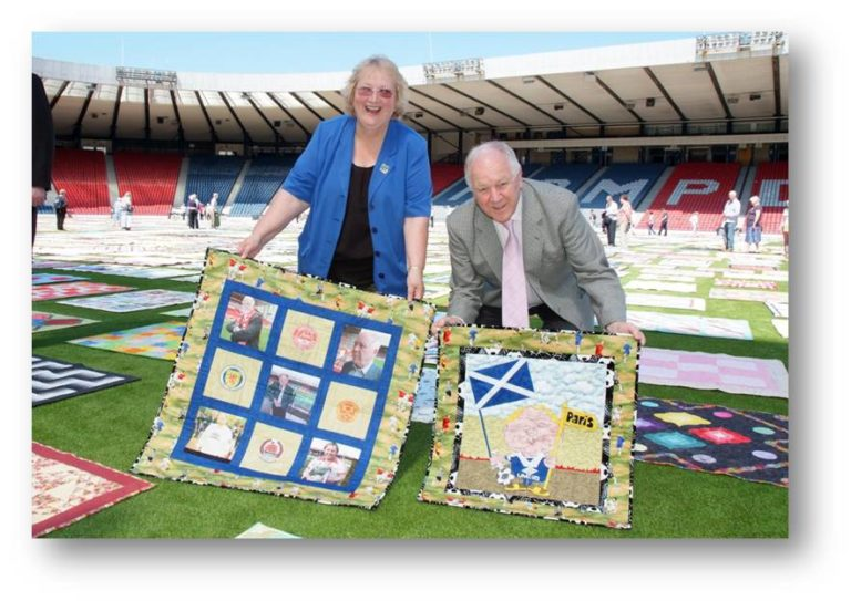 Image of quilter Ann Hill with ex Scotland manager Craig Brown at Hampden Park Pitch
